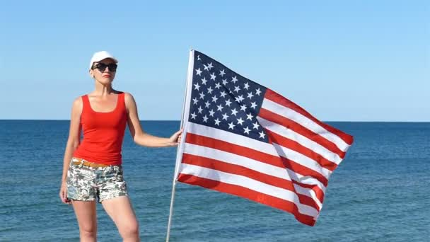 Harmonious  patriotic  pretty woman  stand with American flag near sea.