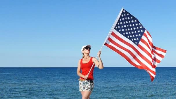 Stojan vlastenecké žena při pohledu na americkou vlajku blízko moře.