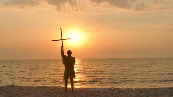 4. křesťanské modlitbě člověk asketa, mnich pobyt s kříž proti západu slunce na seacost