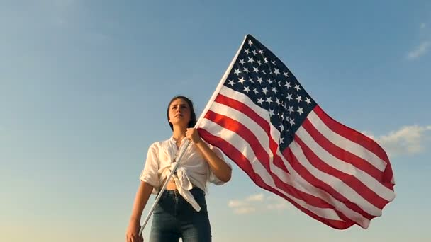 Serious girl teenager  stand with American flag against blue sky. Slow motion