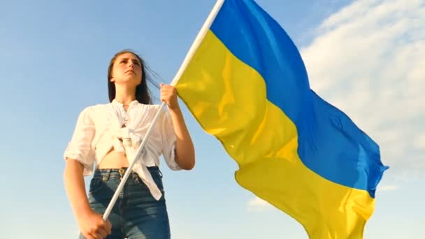 Serious girl teenager stand with Ukrainian  flag ,look forward .Slow motion