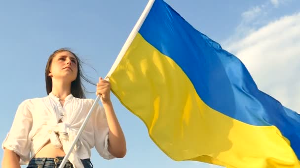Girl teenager stand with Ukrainian  flag ,look forward . Serious  face.Slow motion