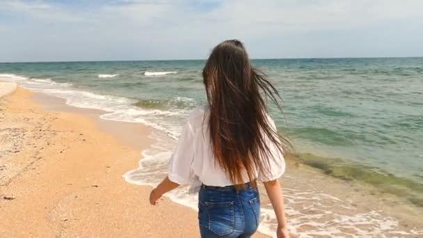 Lány barna tinédzser séta a tengerpart és megfordul, lassú mozgás, lassan a testtel szemcsésedik. Hátulnézet