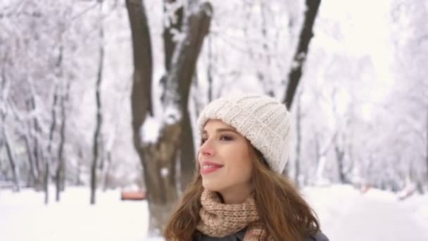 4 k. zimní krásy. Vycházkové, usmíval se hezká žena v bílém klobouku procházky v parku. Stabilní záběr