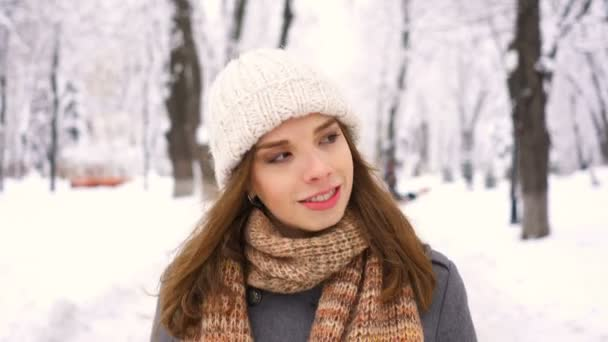 4k. Walking pretty   woman in white hat  walking  in park. Steady  shot, winter time