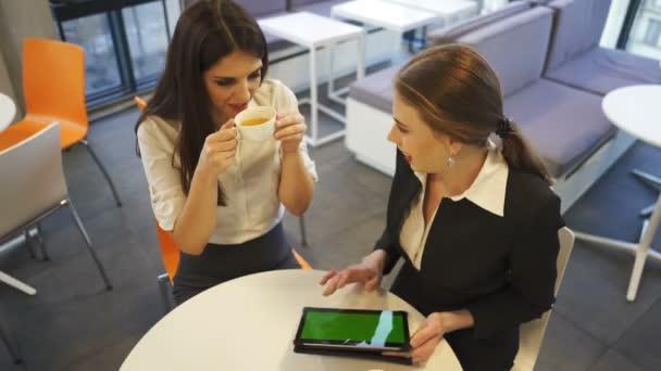 4. két mosolygó üzleti nők zöld képernyő tabletta nézni, és megvitassák, folyamatos lövés. Office stílusú csapat szobában kávé