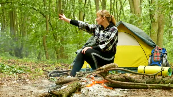 4k.Woman tourist near  tent and campfire do selfie by mobile with flash. Outdoor life