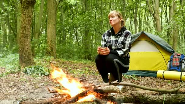 4k. Ženská turistka sedí u stanu a hoří s kávou. Venkovní život