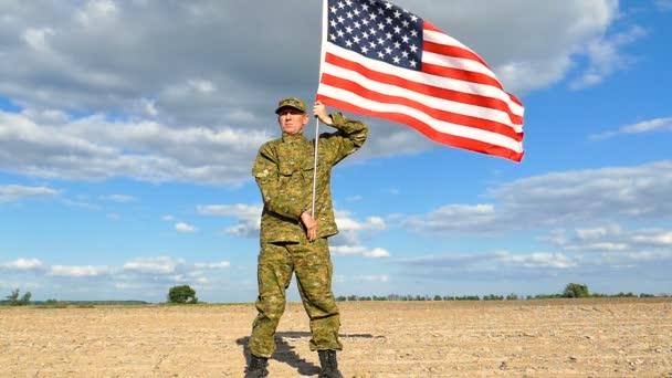 A katona az amerikai zászlót a kék égre tartja. Kültéri lassított jelenet