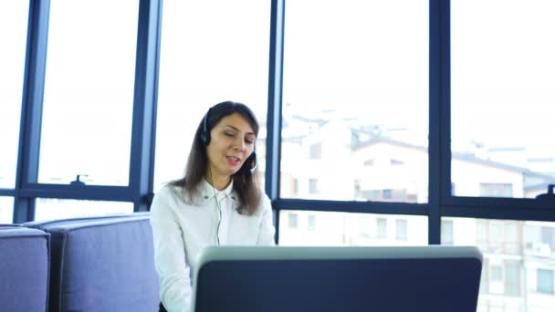 4K. Call center work. Woman operator in white blouse answer client in office