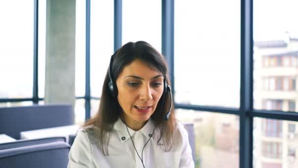 4K. Woman call center  operator answer client, using laptop. Slider shot