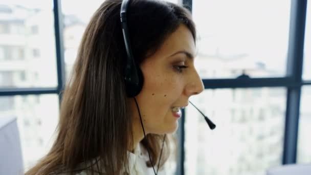 4K. Office call center work. Woman operator in earphones answer client, slider shot