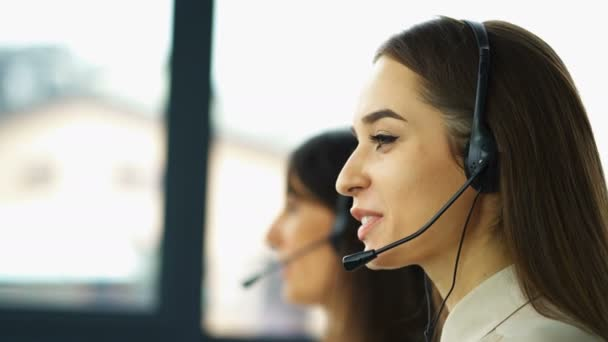 4K. Office call center work. Two young women operators answer client