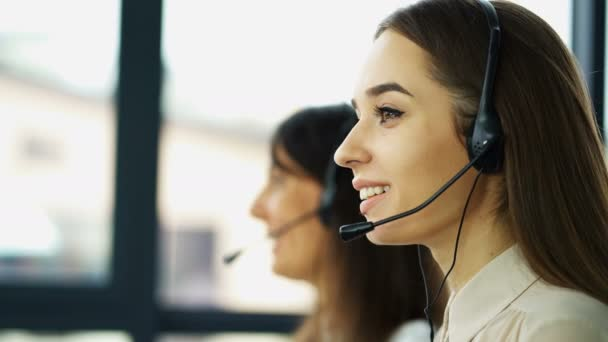 4K. Office call center work. Two young pretty women operators answer client