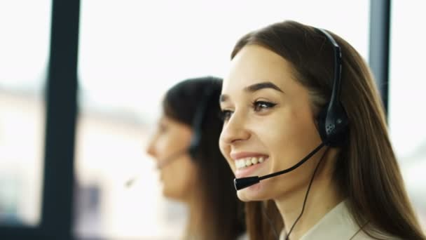 4K. Office call center work. Two young smiling women operators answer client