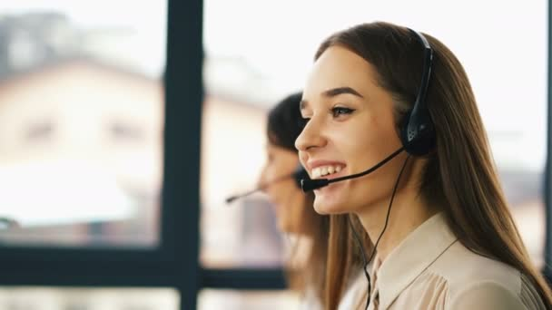 4K. Two young smiling women operators answer client. Office call center work.