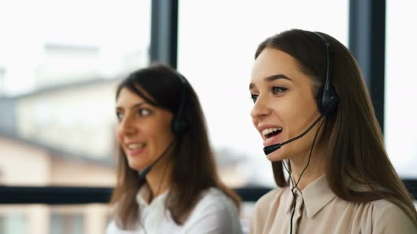 4K. Call center work. Two young pretty women operators talk with client by earphones