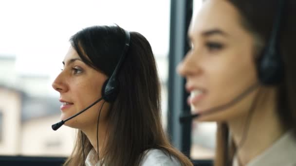 4K. Call center. Two young pretty women operators talk with client by earphones