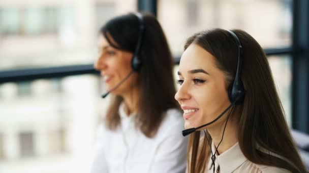 4K. Two young smiling women operators answer client. Office call center work