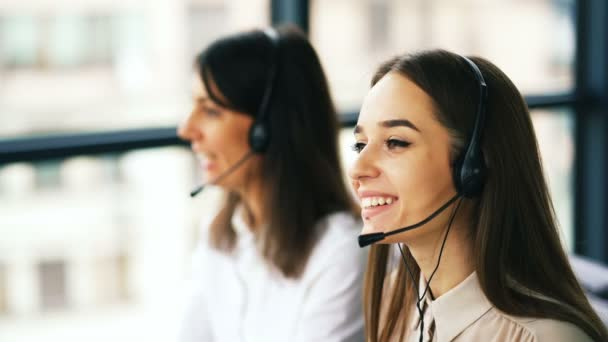 4K. Two young smiling women operators answer client by earphones. Call center work