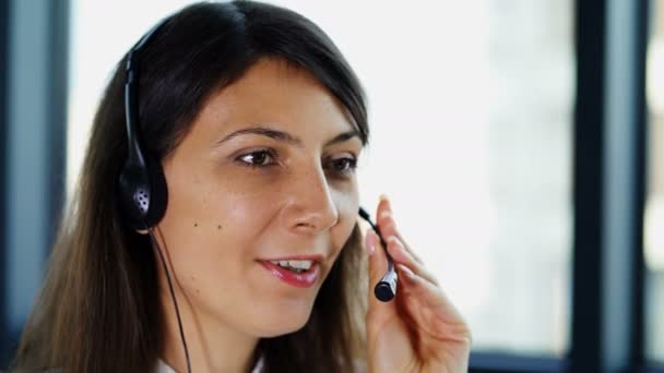 4K .Call center work. Woman operator in earphones answer client in office and look at camera