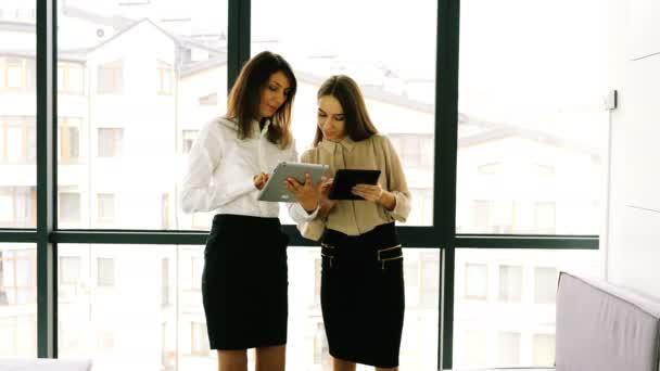 4. zwei junge attraktive Geschäftsfrauen arbeiten mit Tablet im Büro