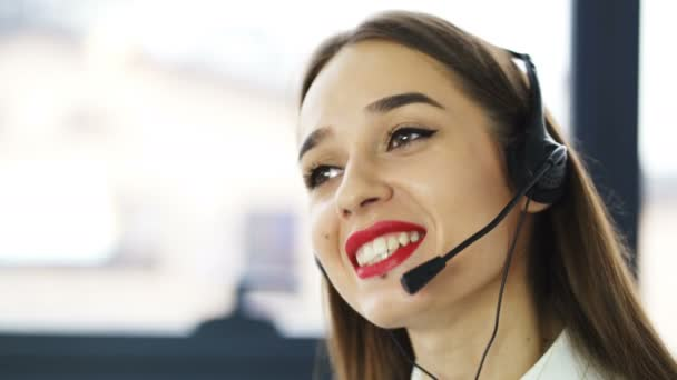 4K .Call center. Pretty woman operator in earphones answer client in office