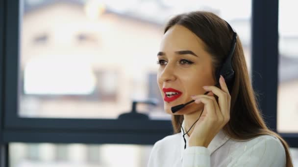 4K . Pretty woman operator of call center answer client in office and look at camera