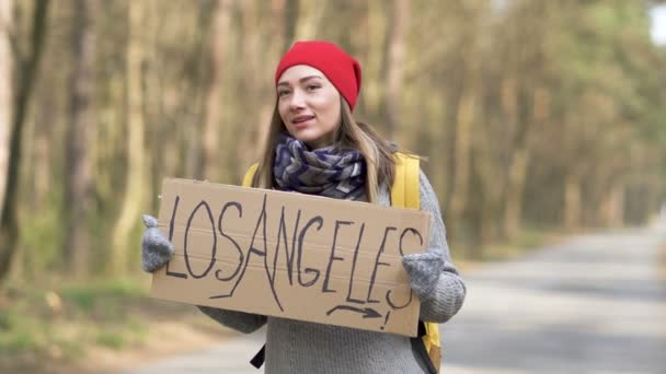 Hitchhiking girl  stay on empty road in wood with poster Los Angeles. Travel is life
