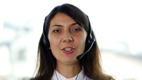 4K. Pretty woman operator in earphones answer client.Portrait