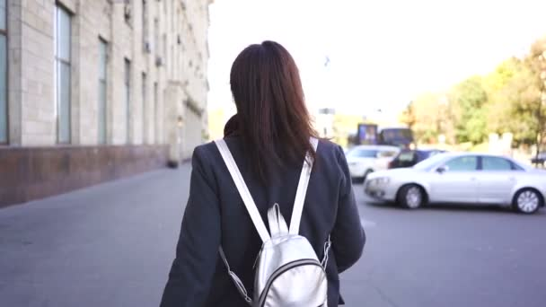 Young   Asian woman in city street turn back and smile. Steady shot, slow motion
