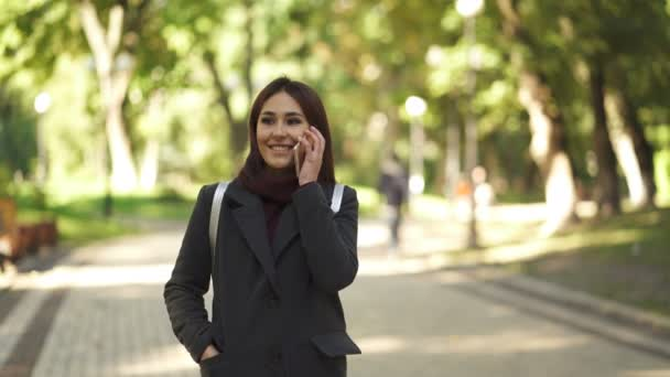 4k. Pretty  young Asian woman talk by mobile smartphone in city park.