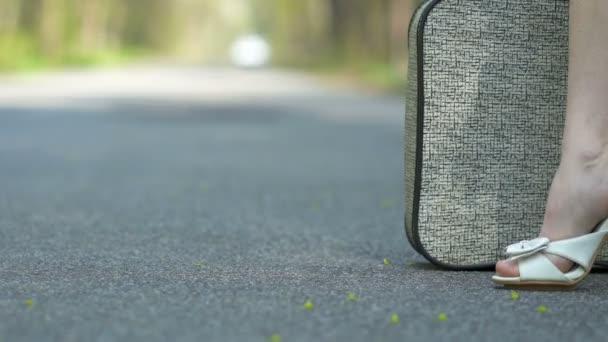 4k. nohy ženy na vysokých podpatcích u retro kufru na silnici