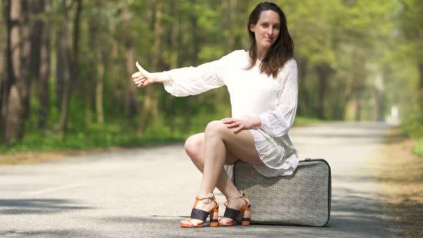 4k.junge trampende hübsche Frau sitzt auf Retro-Koffer