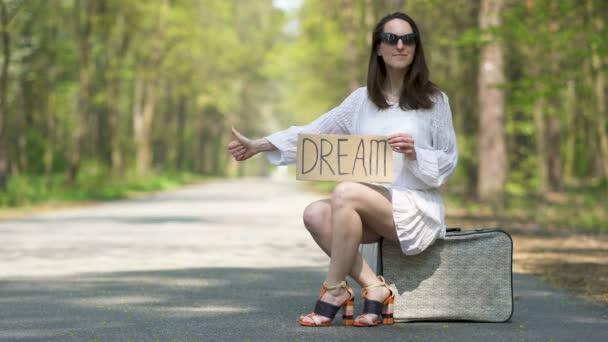 4k. Woman autóstoppal ül retro bőröndon, poszter Dream. Ujjunkkal felfelé