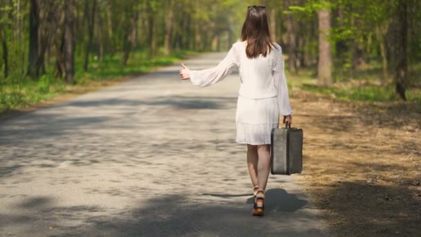 4K.Woman hitchhiking go with retro suitcase ,summer travel team
