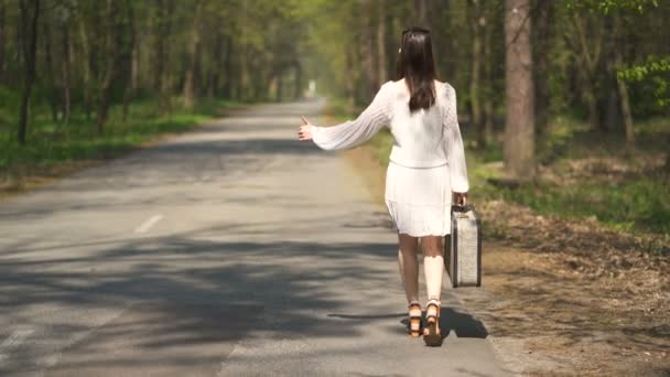 4K.Woman hitchhiking go with retro suitcase ,summer travel team.Steady shot