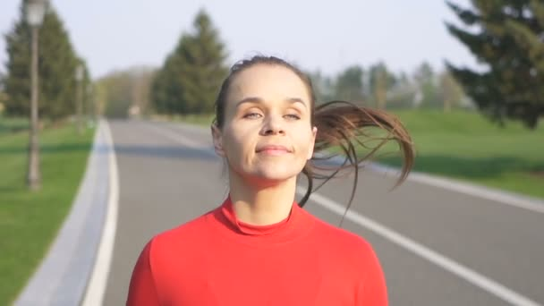 Morning run. Face of happy adult woman runner run on road. Slow motion, steady shot