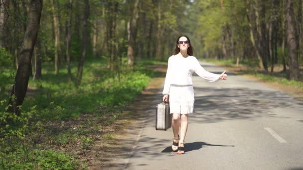 4k.junge trampende hübsche Frau mit Retro-Koffer auf der Straße in Holz. Reiseteam