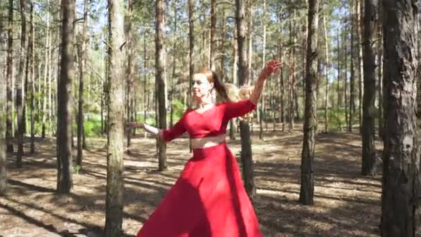 Modern contemporary dancer improvisation. Skill ballerina woman in red dress dancing in  summer forest landscape.