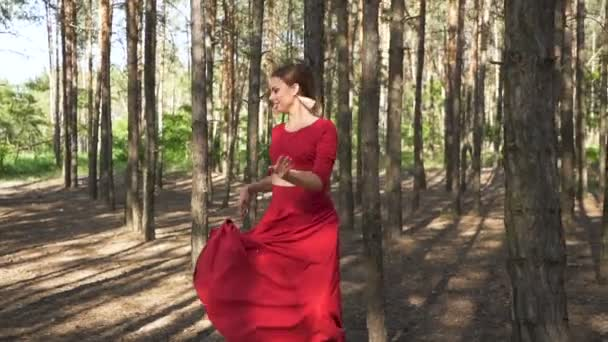 Contemporary dancer improvisation. Skill ballerina woman in red dress dancing in forest landscape. Slow motion