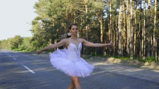 Ballet dance improvisation . Pretty skill woman ballerina in tutu dancing on road. Steady shot