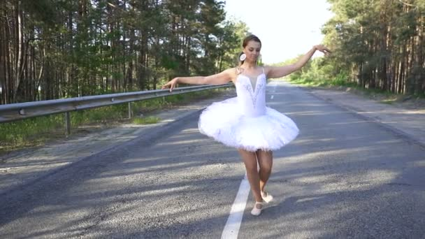 Skill modern woman ballerina in tutu dancing on road. Slow motion, ballet  dance improvisation
