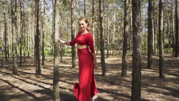 Kortárs ügyességi nő balerina piros ruhában táncolnak az erdőben. A balett improvizáció szépsége