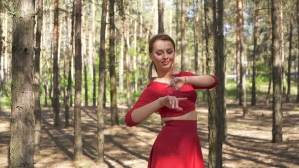Soudobá dovednostní tanečnice v červených šatech tančících v lese. Improvizace