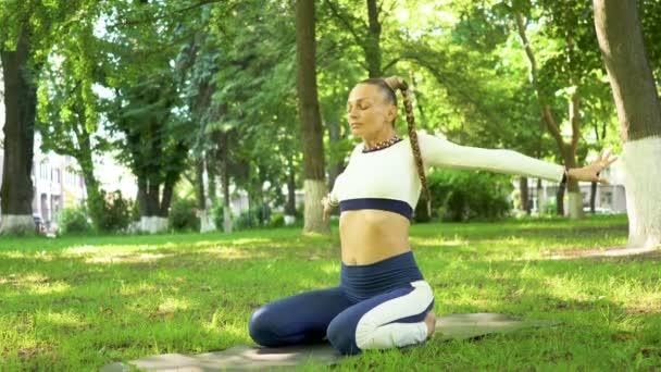 4K.Woman in spring park do meditation exercises of yoga