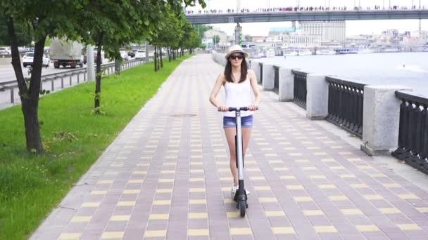 Zpomaleně. Dívka v klobouku jezdila na elektrický skútr v městské oblasti blízko řeky. Stálá střela