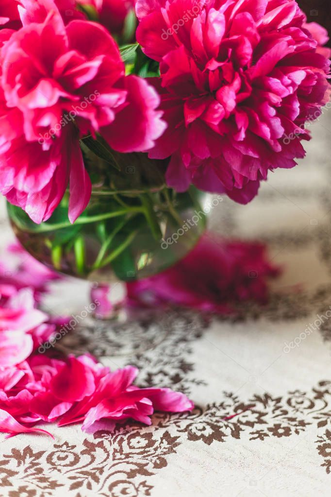 peonies on the table. Bright red flowers on short legs stand in a transparent vase. On the table lie fallen peon petal