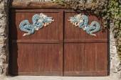 Brána do buddhistického chrámu. Hnědá dřevěná vrata se dvěma krásný modrý drak