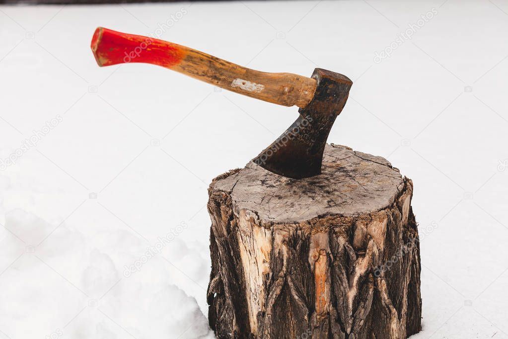 ax sticks out in a stump on white snow on a winter da